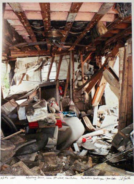 From the series of photographs by Steven L. Smith; image of a gutted house. The walls and ceiling are stripped to the bare studs. Insulation hangs from the open ceiling. There is a lot of refuse in the center of the room including clothes and furniture.
